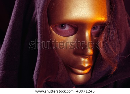 The person with long hair in a gold mask - stock photo