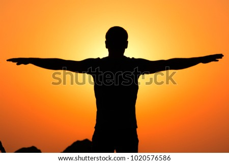 The photo expose a young boy facing the rising sun over the ocean expressing nothing but happiness and freedom