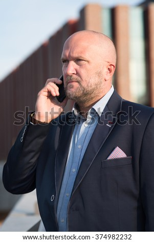 The photo shows a businessman using mobile phone.