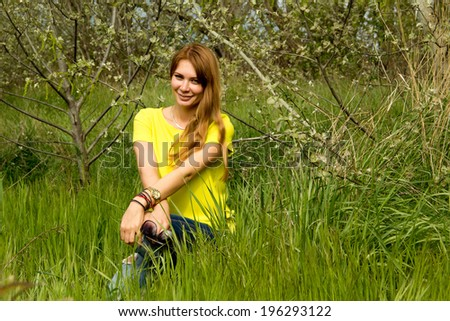 The photo shows a girl in a yellow blouse and blue jeans. Picture taken in the countryside.