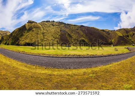The photo was taken Fisheye lens.  On canyon there is dirt road. Camping in the canyon Pakgil, Iceland. The canyon -  green grass and moss on fantastic rocks - stock photo