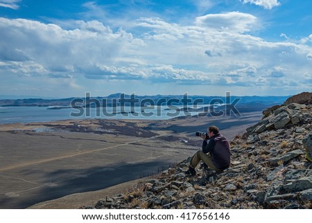 the photographer sits on the hill overlooking lake Baikal