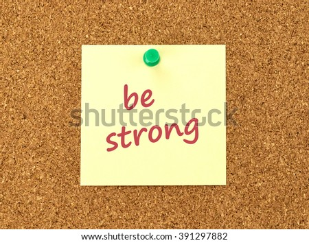 The phrase Be Strong in red text on a yellow sticky note posted to a cork notice board.
