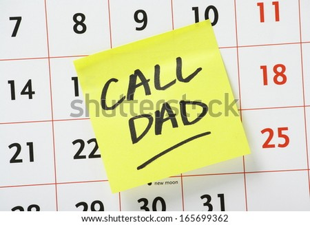 The phrase Call Dad written on a yellow sticky paper note and stuck to a wall calendar. - stock photo
