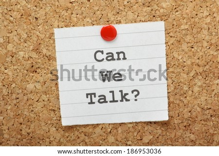 The phrase Can We Talk typed on a paper note and pinned to a cork notice board