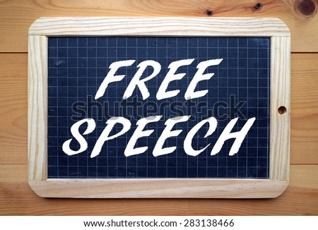 The phrase Free Speech in white text on a slate blackboard placed flat on a wooden surface