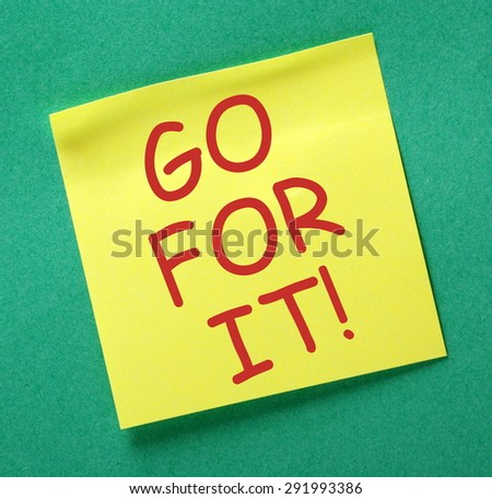 The phrase Go For It in red text on a yellow sticky note posted on a green notice board - stock photo