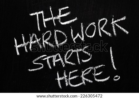 The phrase The Hard Work Starts Here written by hand in white chalk on a used blackboard - stock photo