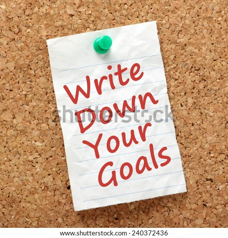 The phrase Write Down Your Goals written on a piece of paper and pinned to a cork notice board as a reminder - stock photo