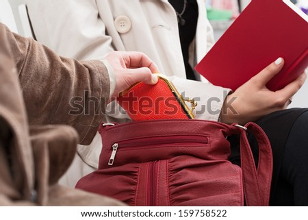 The pickpocket is stealing the woman's wallet - stock photo