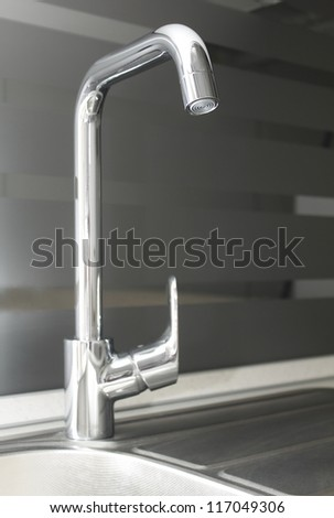 The picture shows a chrome kitchen faucet