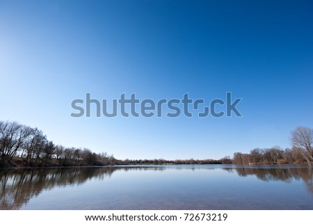 The picture shows a lake which is partly covered with a thin layer of ice and a cloudless sky. - stock photo