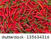The picture shows a pile of small, red, very hot and spicy chilli peppers on an asian market. - stock photo
