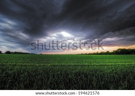The picture shows a storm brewing over a field. - stock photo