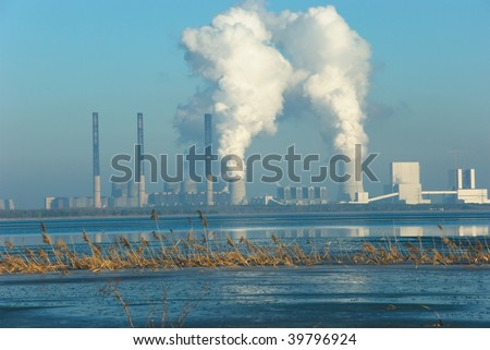the picture shows the coal power station boxberg on a cold winter day with the baerwalder see in front of it