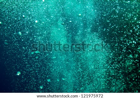 The picture shows underwater bubbles which raise from the depth of blue sea - stock photo