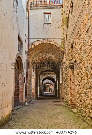 the picturesque covered street Via delle Volte, a medieval narrow alley in Castellina in Chianti, Siena, Tuscany, Italy 