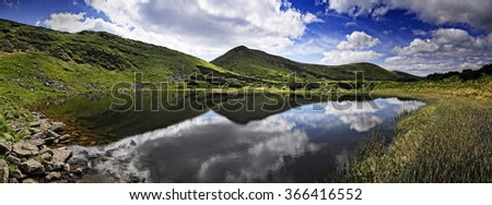 The picturesque lake surrounded by mountains. The lake reflected the clouds