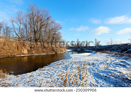 The picturesque landscape of the freezing river and oak trees without leaves on snowy shore on a sunny day in early winter - stock photo