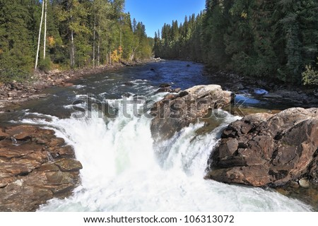 The picturesque waterfall in the Rocky Mountains of Canada. The river flows through a dense forest. Sunset in Jasper National Park - stock photo