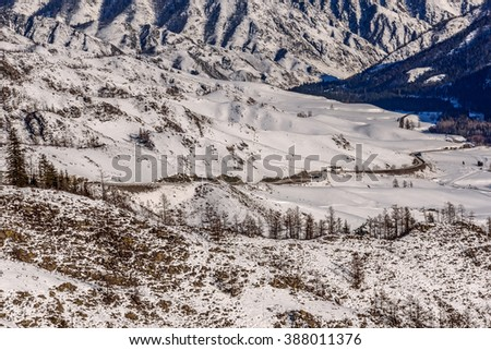 The picturesque winter top view on the mountains covered with snow, the valley between the mountains, the trees and asphalt winding road  - stock photo