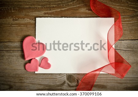 the piece of paper lying with hearts and ribbon on a wooden background - stock photo