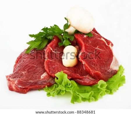 the piece of raw fillet steak with mushroom salad and garlic isolated on white background. - stock photo