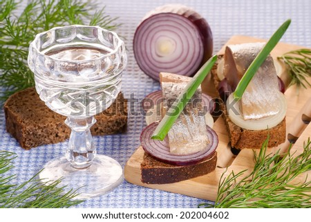 The pieces of salted herring on rye bread with slices of red onion decorated fresh green and the glass on blue napkin. Selective focus. - stock photo