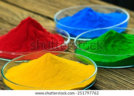 The pile of powder coating on glass plate, on wooden background.