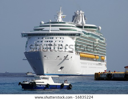 The pilot boat meets the cruise liner that is arriving to Cozumel island, Mexico. - stock photo