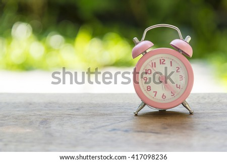 the pink analog alarm clock with the garden background - stock photo