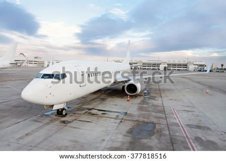 The plane at the airport on parking area - stock photo