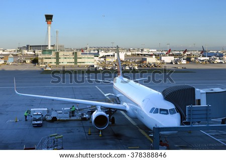 The plane stands with the tunnel at the airport in London. Aircraft is prepared for departure from Heathrow airdrome.