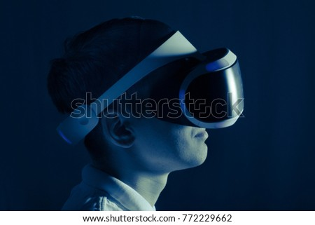the player with VR helmet  is lit by light from a computer screen.
