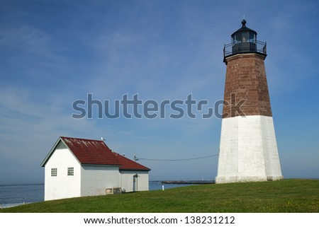 The Point Judith light and associated buildings near Narragansett, Rhode Island, against a bright blue sky and whispy white clouds - stock photo