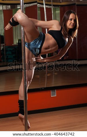 The Pole-dancer performs a dance figure in the gym with Pole