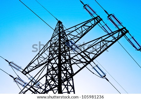 the poles of a power line against a blue sky. high voltage power line - stock photo