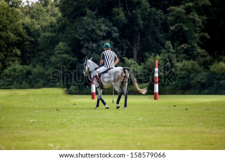 The Polo Referee is riding in front of the goal. - stock photo