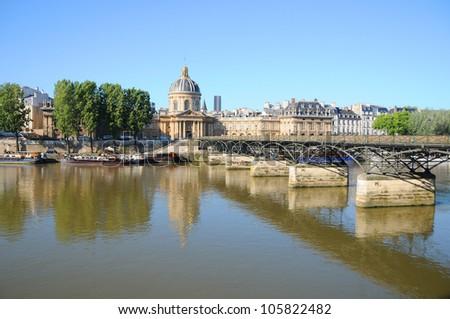 The Pont des Arts or Passerelle des Arts is a pedestrian bridge in Paris which crosses the Institut de France.With Institut de France in background - stock photo