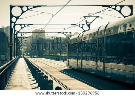 The Porto Metro Train crosses the Dom Luis 1 Bridge over the River Douro at Sunny Day. Toned image - stock photo