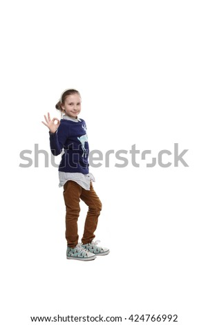 the portrait of a adorable  little teenage girl with a toy in one hand and other hand  shows gesture thumbs up isolated on white - stock photo