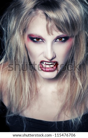 The portrait of a blond girl vampire with bloody streaks - stock photo