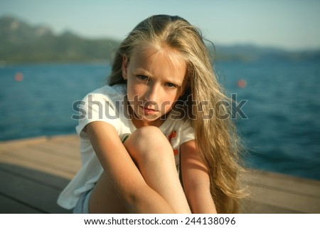 The portrait of the young girl about 9-12 years old with the blonde and loose hair that sits on the pier in the rays of the setting sun with mountain behind her. She wears top-shirt and shorts.