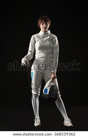The portrait of woman wearing white fencing costume and black fencing mask  with the rapier on black background - stock photo