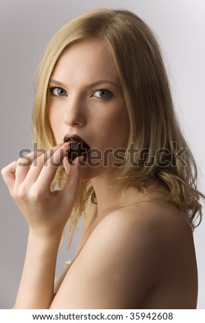 The portrait of young blond girl which holds chocolate candy in to the mouth - stock photo