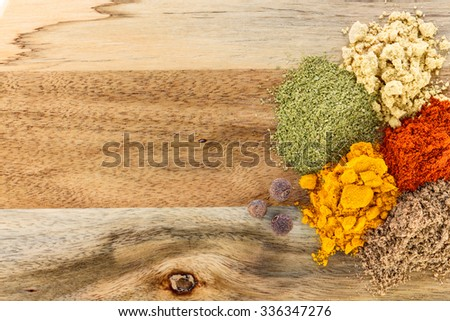 The powders of: bay leaf, turmeric, mustard, red paprika and nutmeg are scattered on the wooden background. - stock photo