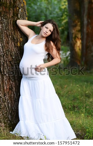 The pregnant woman in summer a tree - stock photo