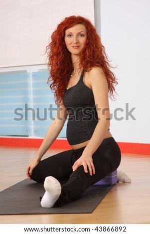 The pregnant woman  is engaged in gymnastics in a sports hall