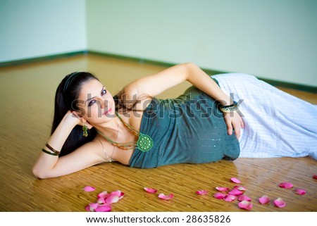 The pregnant young girl among petals of roses - stock photo