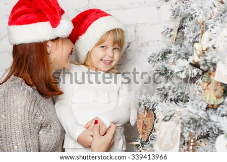 The pretty girl with mum are decorating a Christmas tree in the house. Happy family. - stock photo